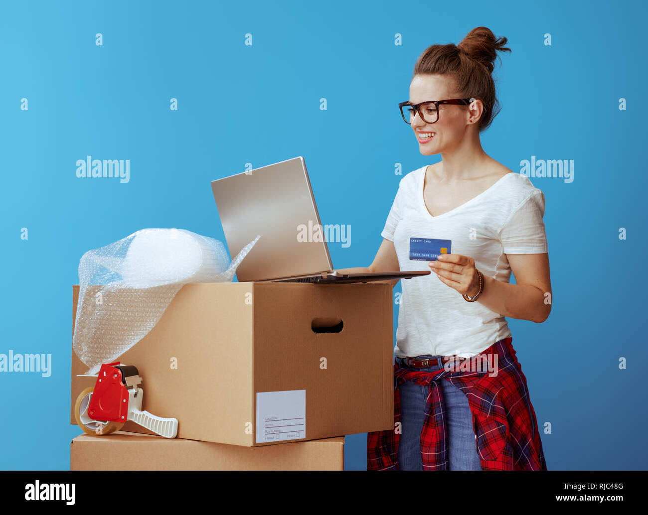 happy modern woman in white t-shirt near cardboard box with credit card using laptop isolated on blue - Stock Image
