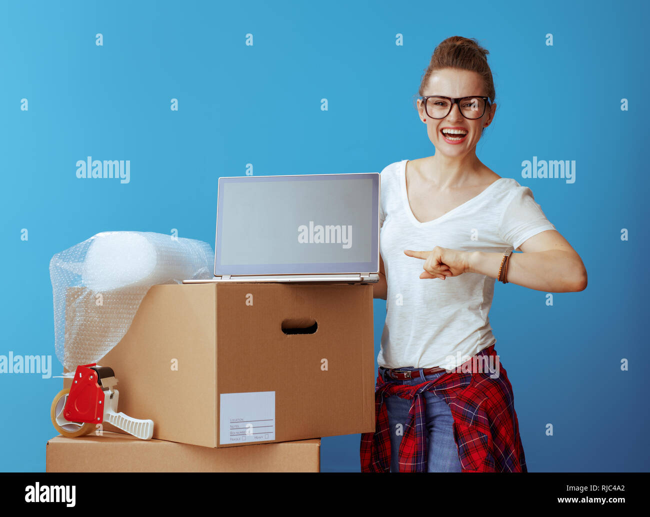 happy young woman in white t-shirt near cardboard box pointing laptop blank screen isolated on blue background - Stock Image