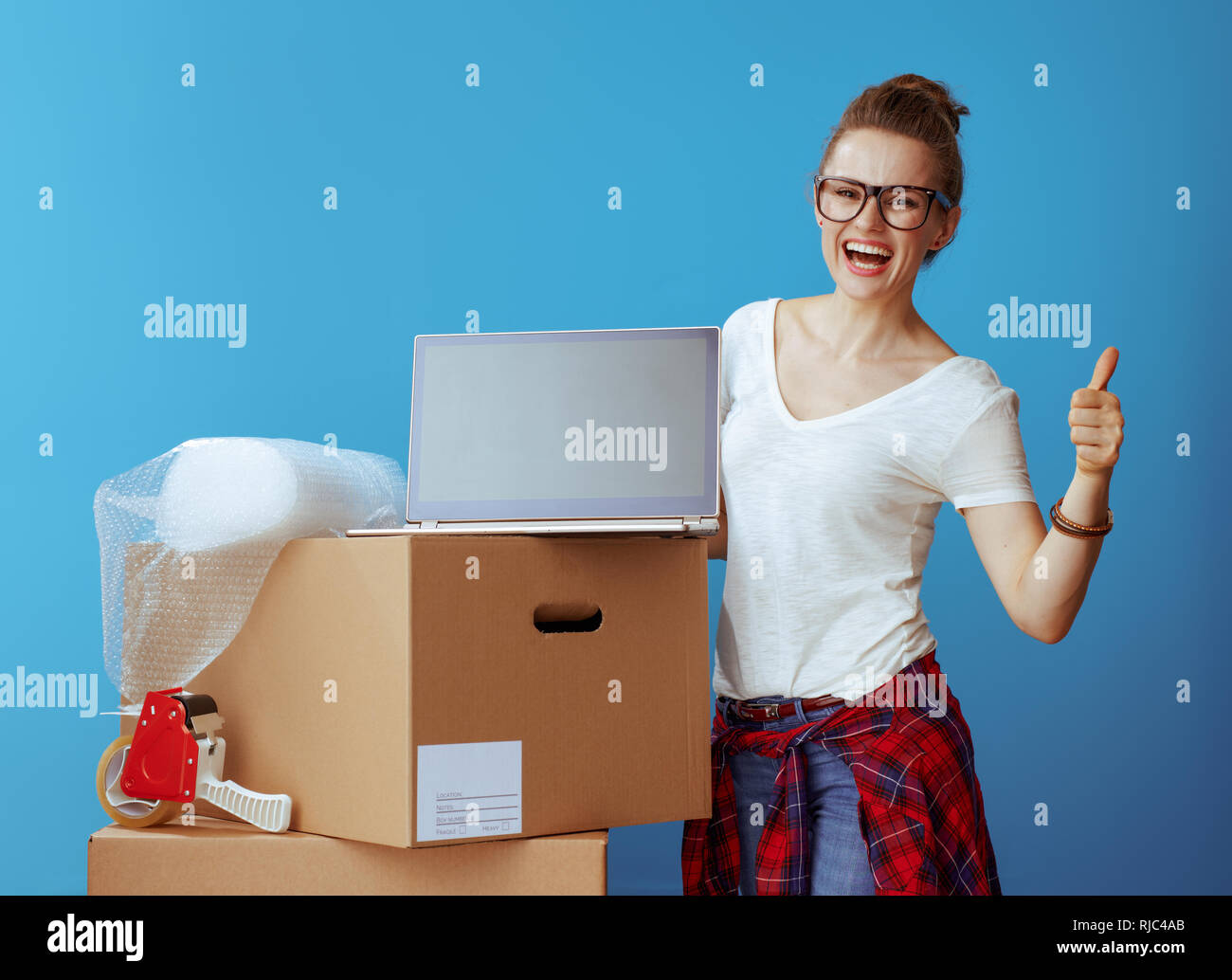 smiling modern woman in white t-shirt near cardboard box showing laptop blank screen and thumbs up on blue background - Stock Image