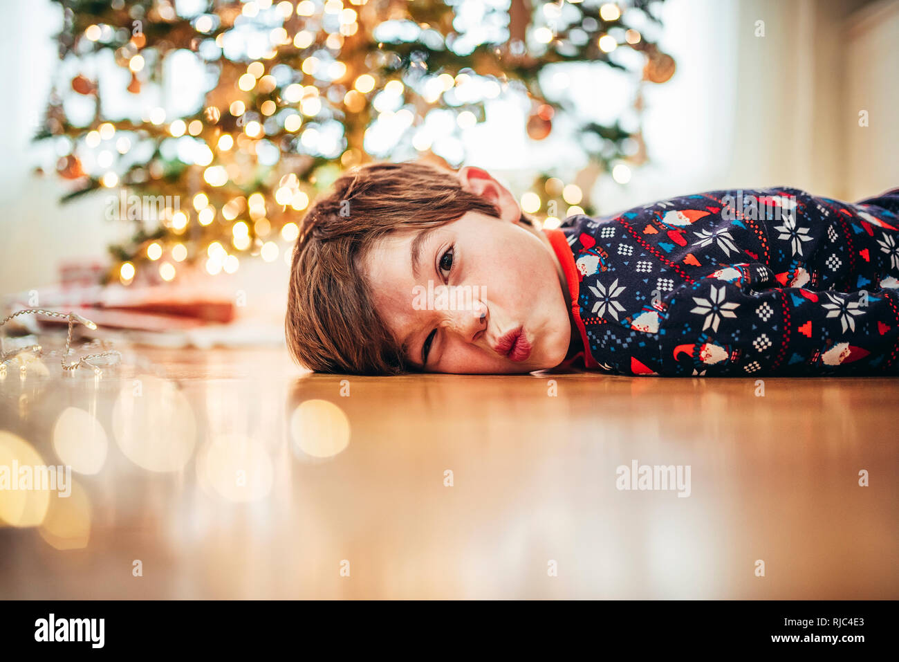 Boy lying on the floor in front of a Christmas tree pulling funny faces - Stock Image