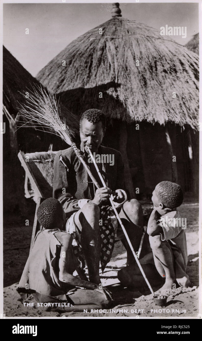 Zambia (Northern Rhodesia) - Storyteller keeping two young boys entranced with his tales. - Stock Image