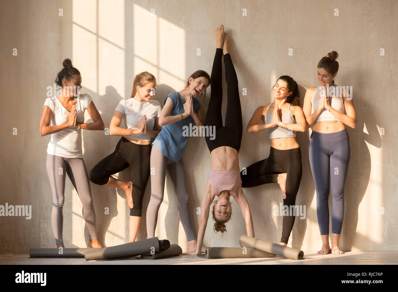 Excited female yogi have fun practicing yoga poses - Stock Image