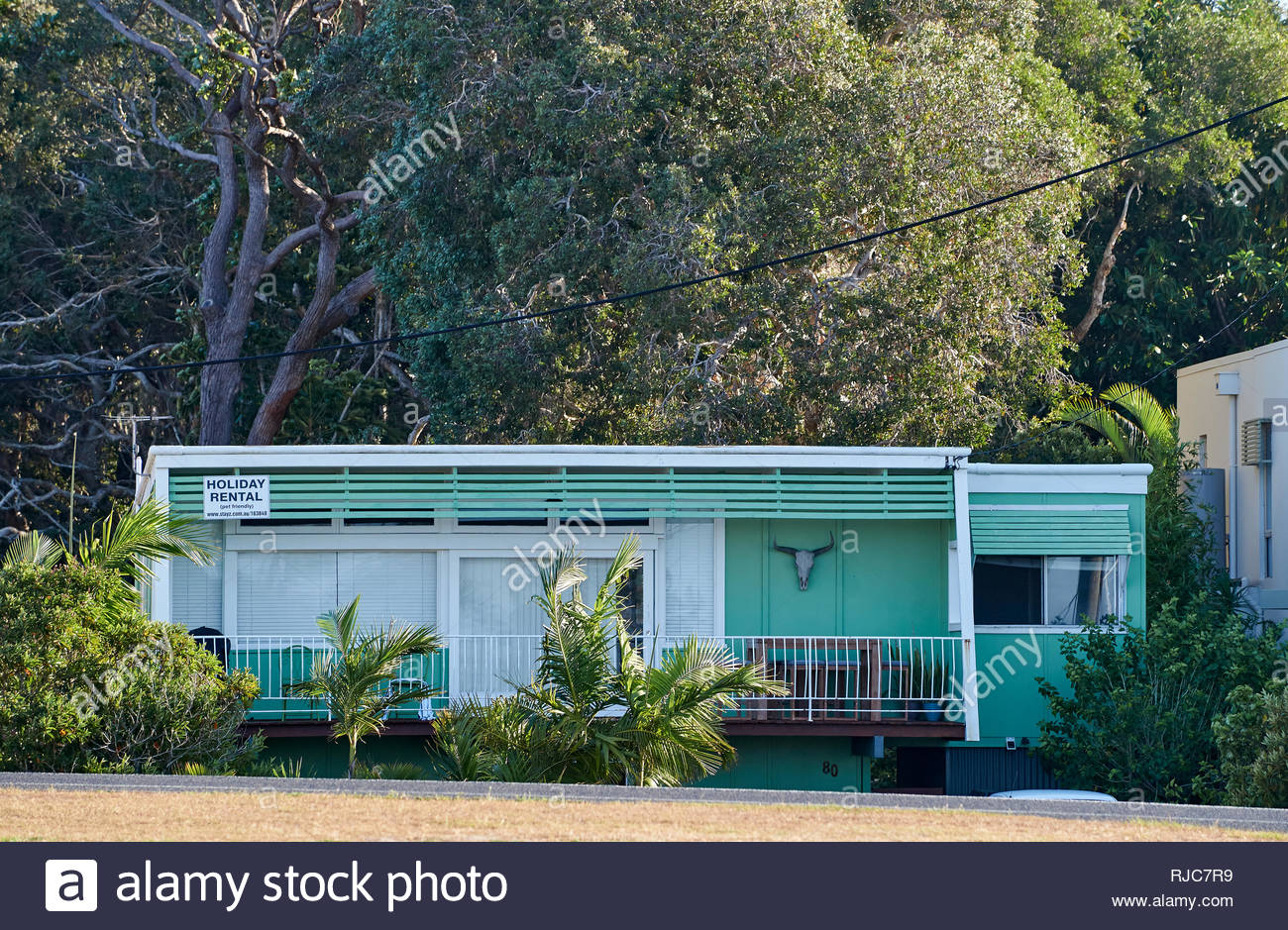 A small - bright green - flat-roofed fibro shack, available for rent during holidays...image taken during a hot summer's day in Yamba, NSW, Australia. - Stock Image