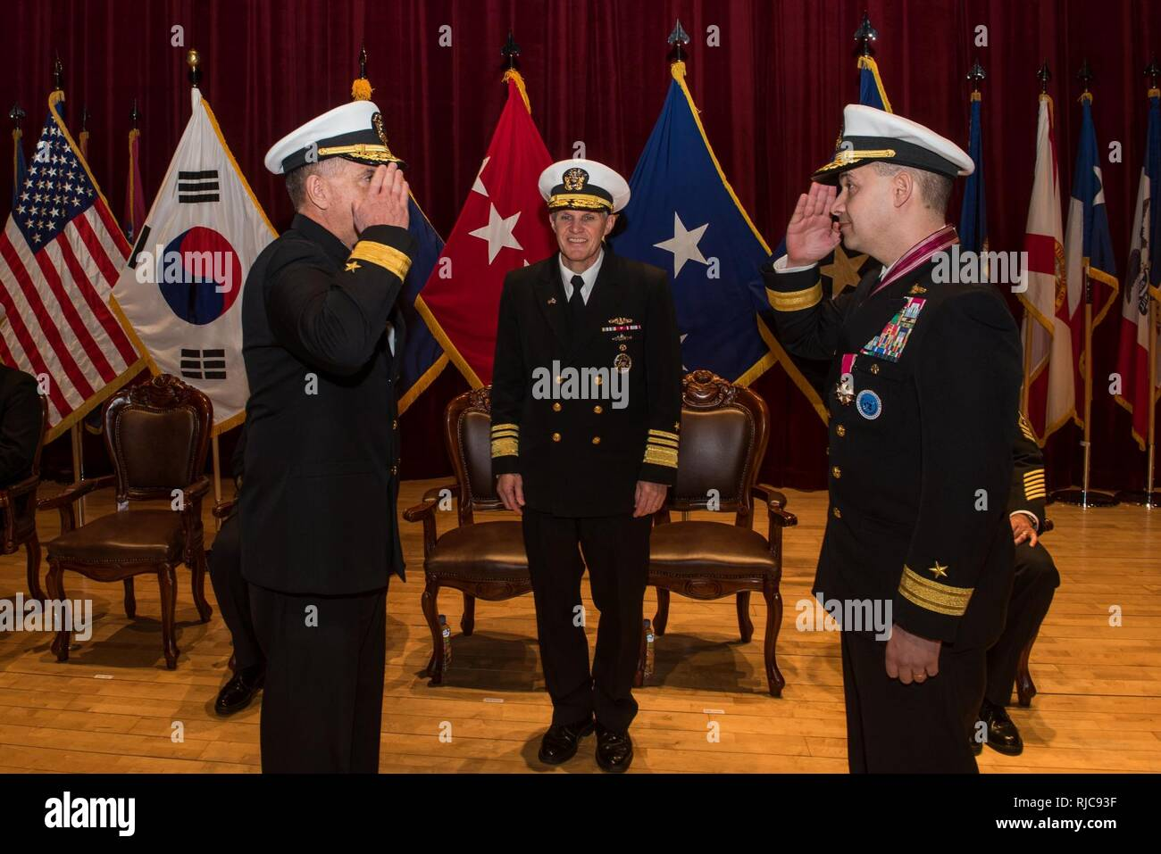 Busan, Republic of Korea (Jan 11, 2018) - Rear Adm. Michael E. Boyle renders a salute to Rear Adm. Brad Cooper in front of Vice Adm. Phil J. Sawyer, commander, U.S. Seventh Fleet, assuming command of U.S. Naval Forces Korea (CNFK). During the ceremony Rear Adm. Michael E. Boyle relieved Rear Adm. Brad Cooper, becoming CNFK's 36th commander. Stock Photo