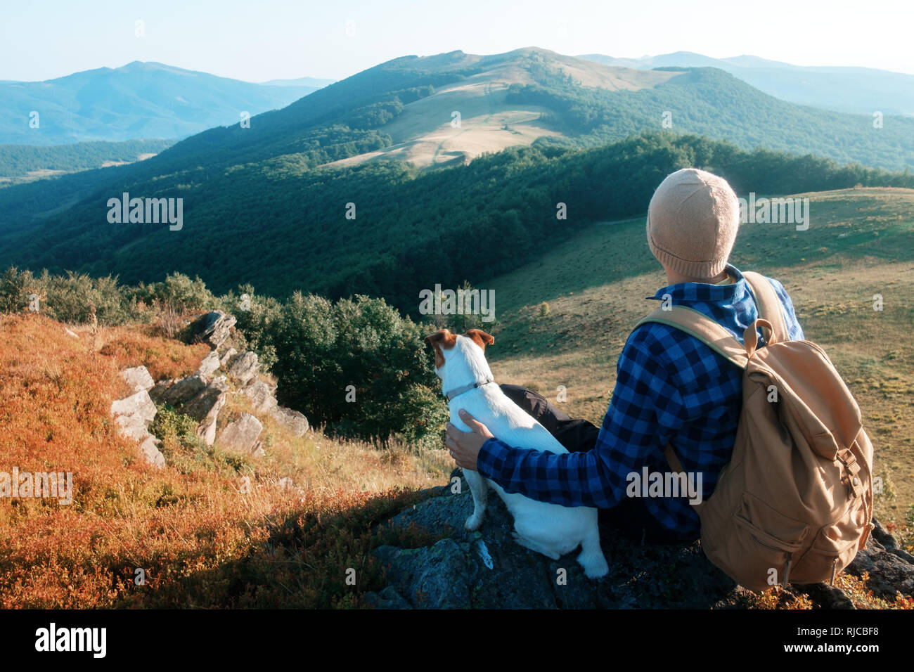 Alone tourist sitting on the edge of the cliff with dog against the backdrop of an incredible mountain landscape. Sunny day and blue sky - Stock Image