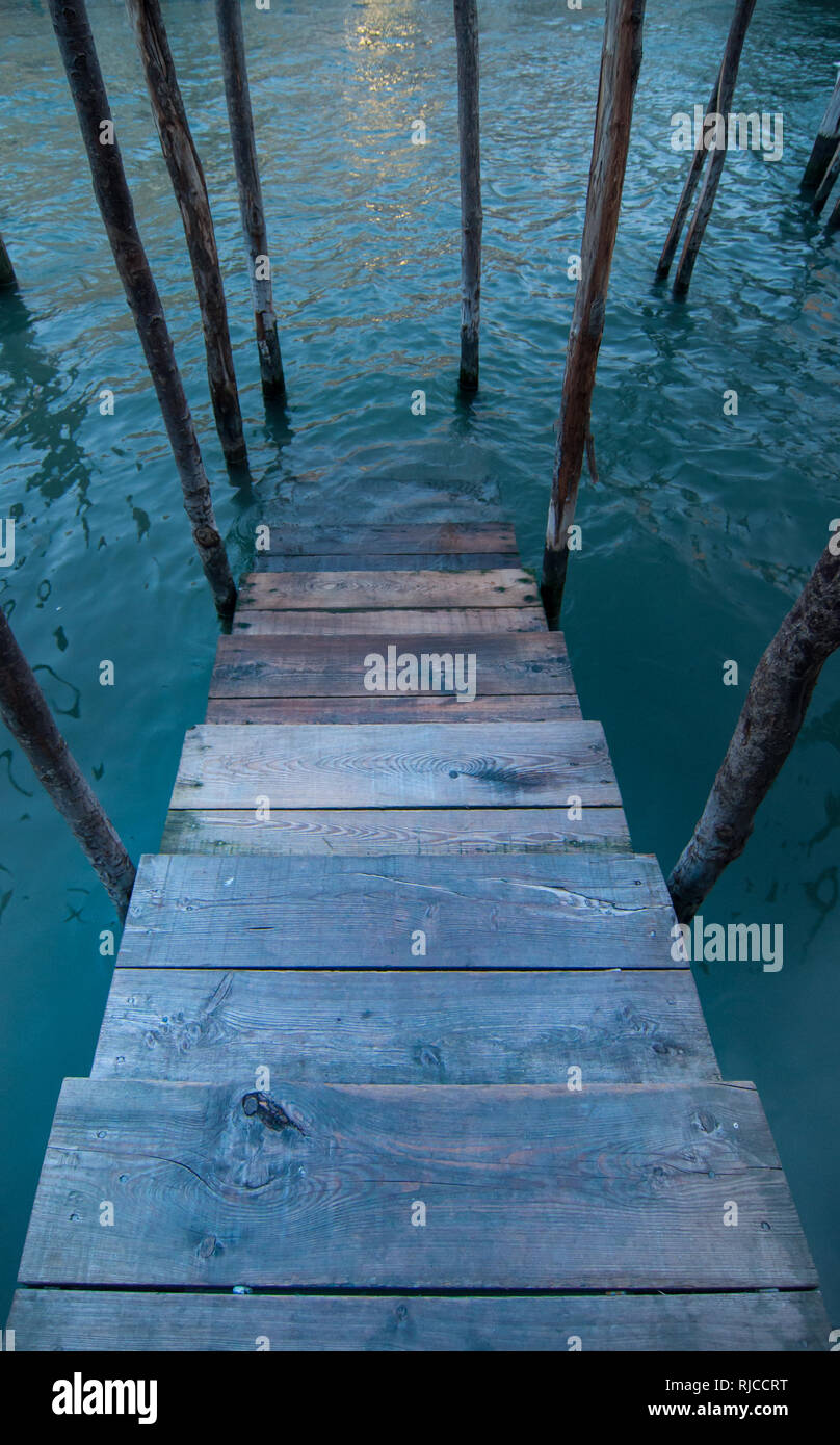 Wooden ladder entering the water in a Venice canal - Stock Image