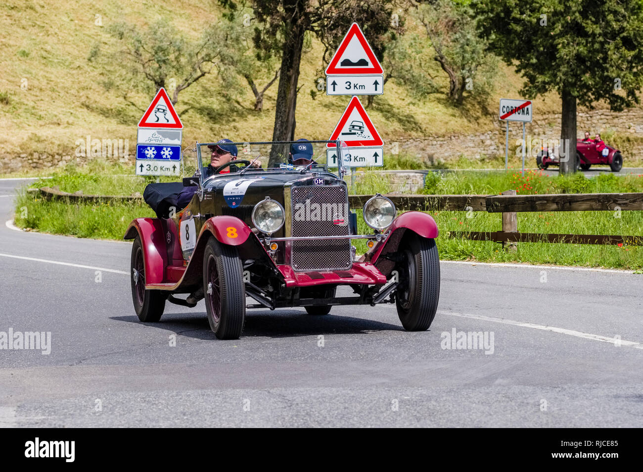 Vintage cars, joining the rallye Mille Miglia, are approaching the medieval town - Stock Image