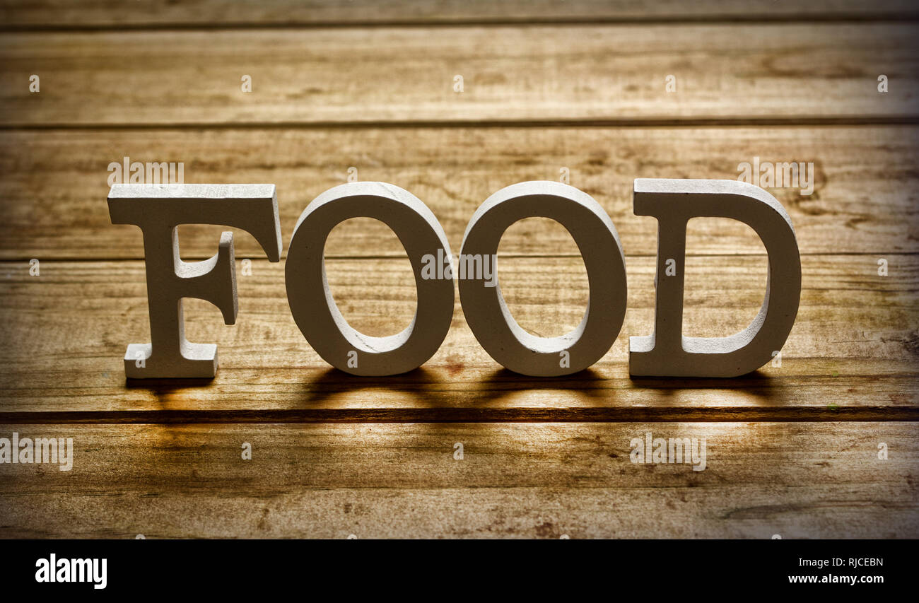 the word food on wooden table - closeup - Stock Image
