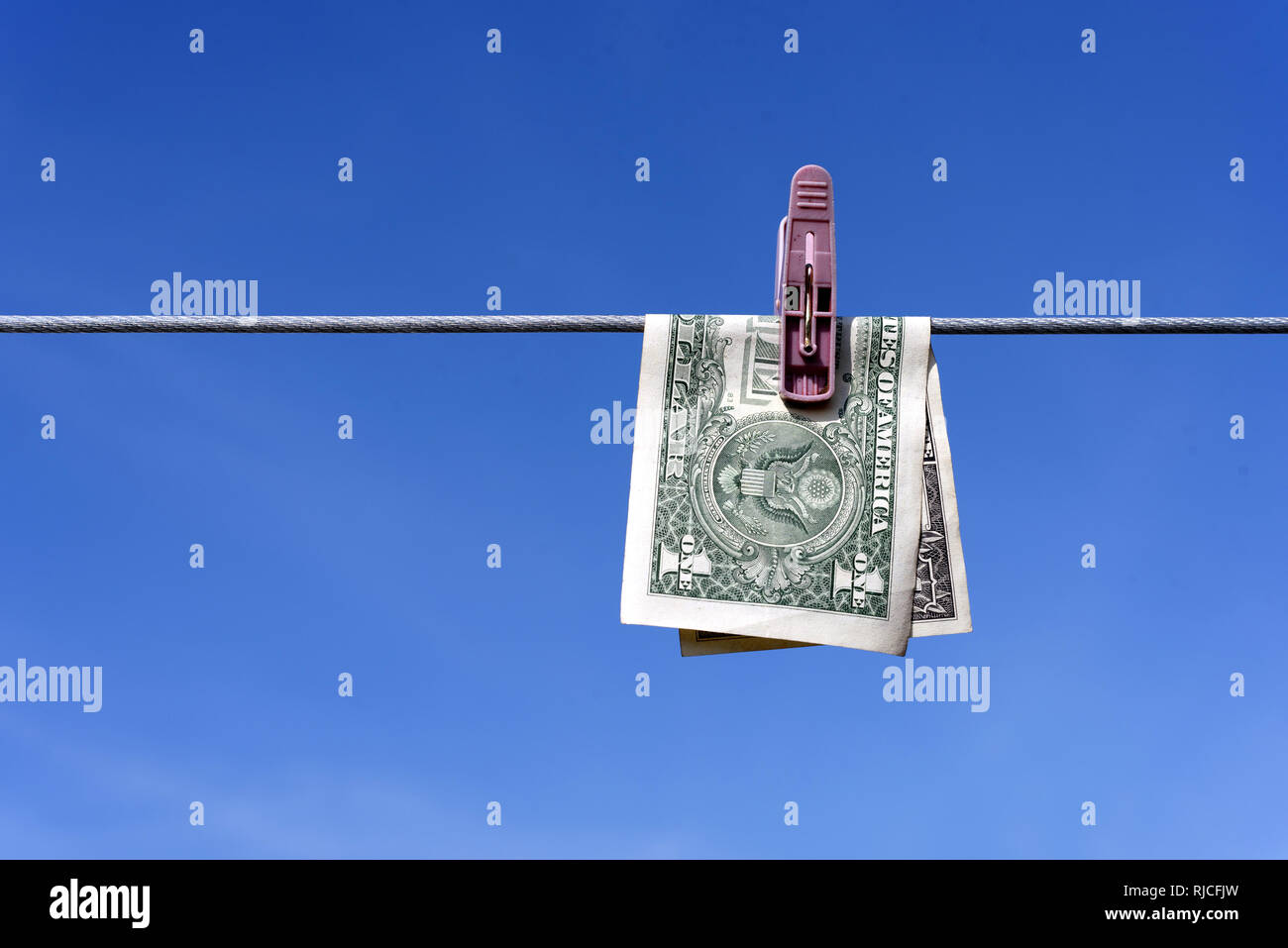 Money laundering of a one US Dollar bill note from the USA on a washing line with blue sky for AML Anti laundering finance business crime ideas Stock Photo