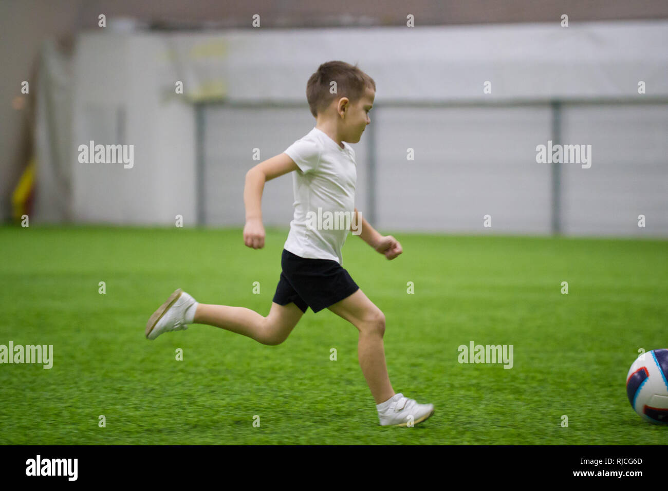 Playing football indoors. A little boy running on the field - Stock Image