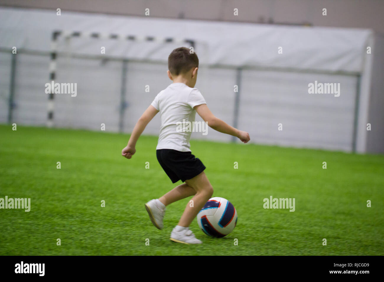 Playing football indoors. A little boy leads the ball - Stock Image