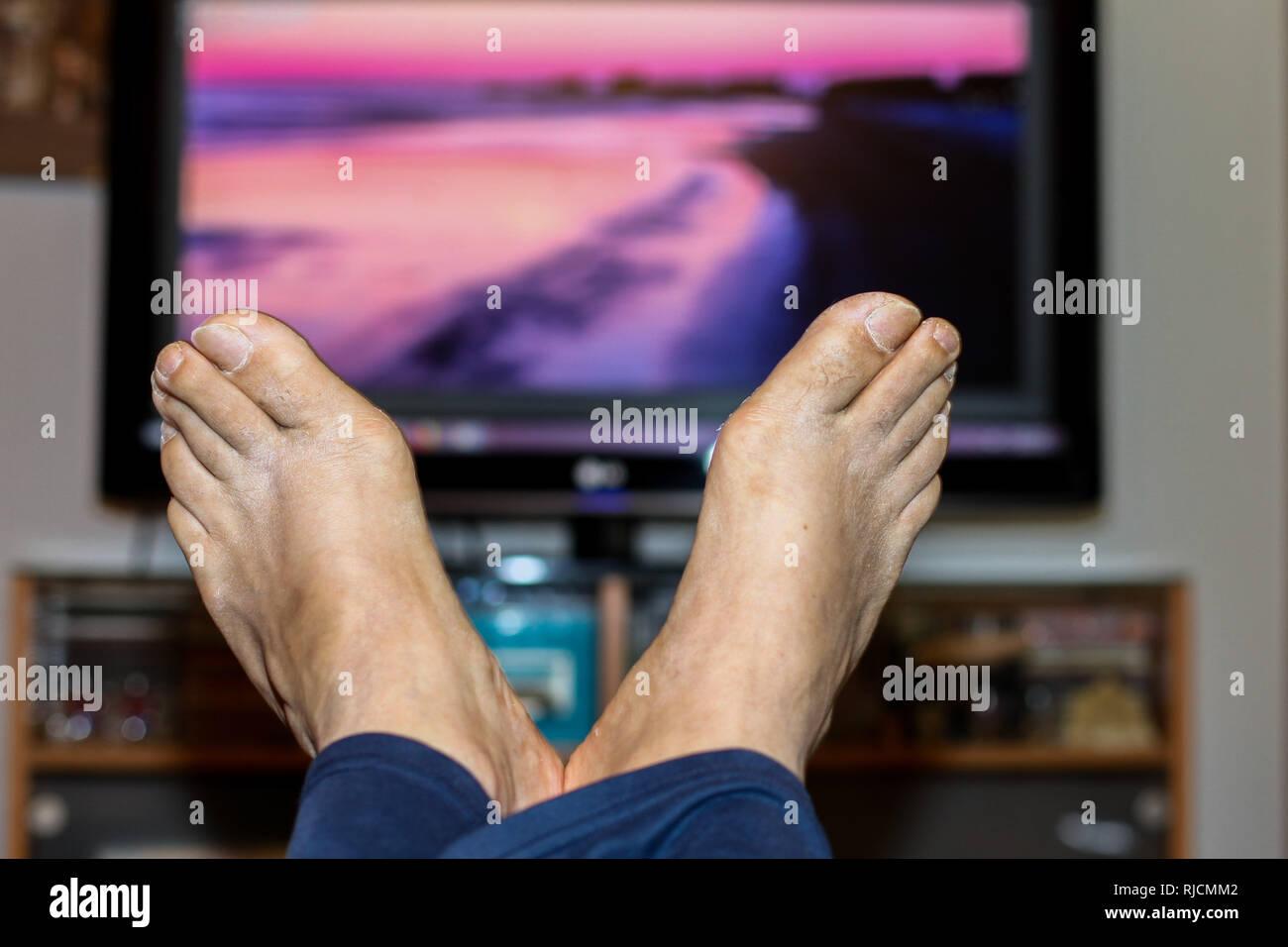 Man legs with beach sunset on tv screen - Stock Image