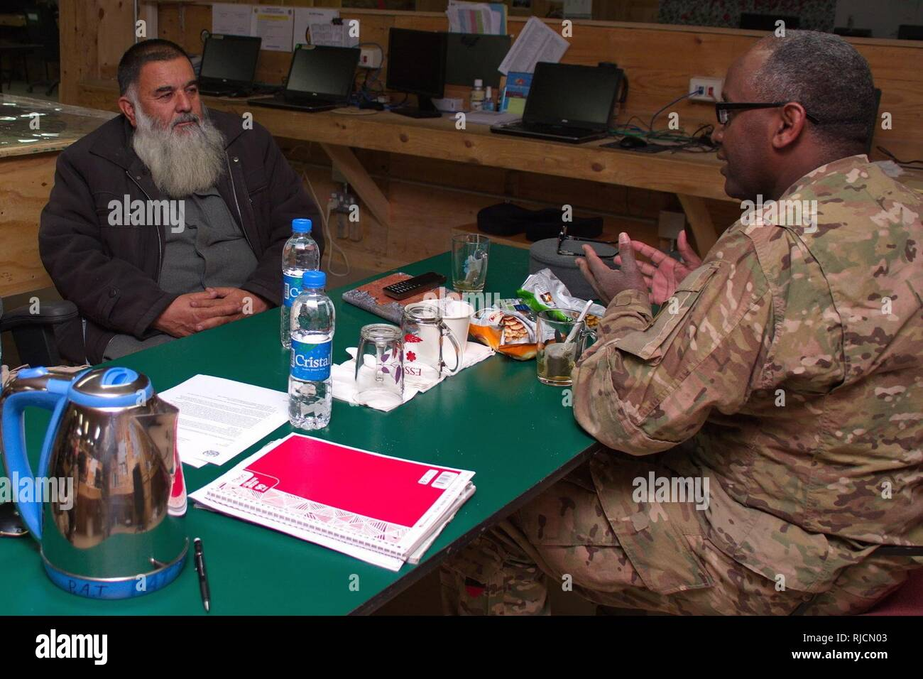 Afghan National Police (ANP) 303rd Zone G1 Commander Col. Zikarullah meets with Task Force Southeast Police Advisor Team (PAT) G1 Advisor Maj. Nuir Hussein of the 3rd Infantry Division Main Command Post Operational Detachment during a key-leader-engagement at Advisory Platform Lightning to discuss training of Afghan personnel on the Afghan Personnel and Pay System (APPS).  APPS is an automated system that generates payroll information for the Ministry of Finance while integrating authorizations, personnel record management and payroll functions into one system for Afghan National Defense and S - Stock Image
