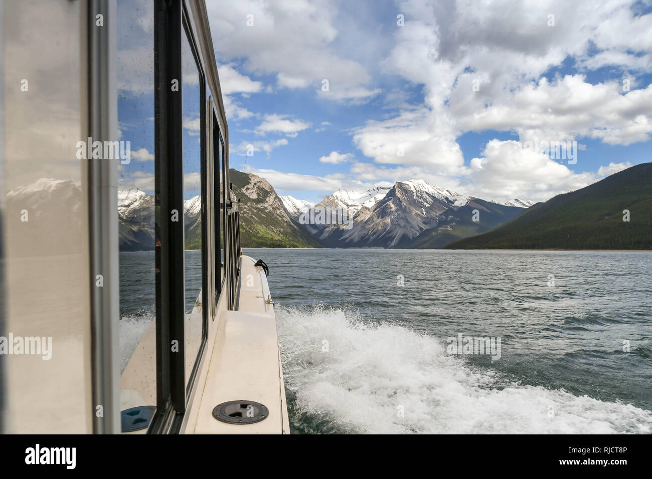 BANFF, AB, CANADA - JUNE 2018: wake of a small tourist boat cruising on Lake Minnewanka near Banff. Stock Photo