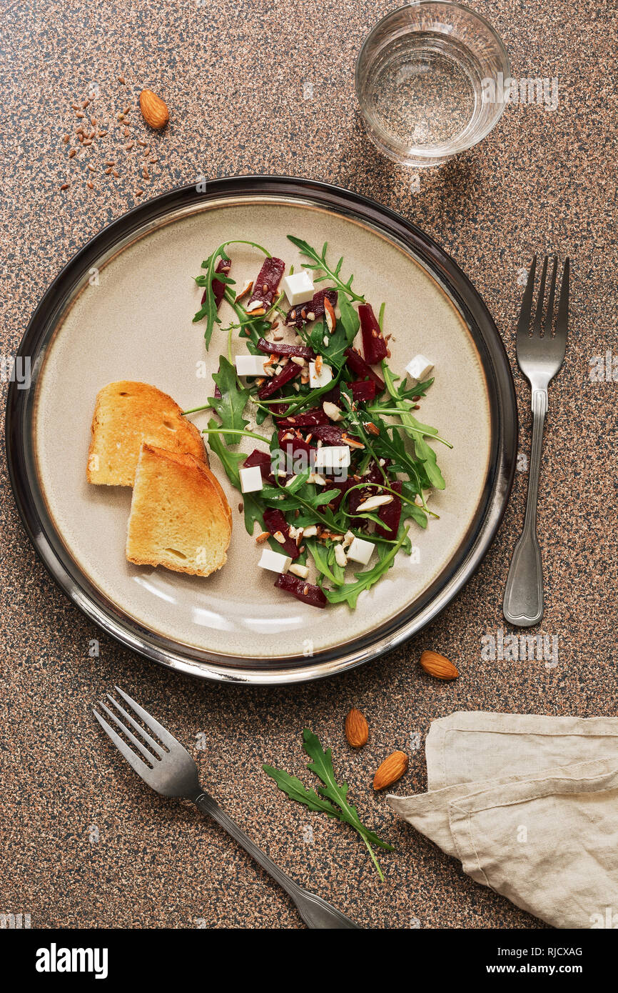 Fresh vegan dietary salad with beetroot, arugula, feta cheese, nuts and seeds over brown stone background. Top view, flat lay. - Stock Image