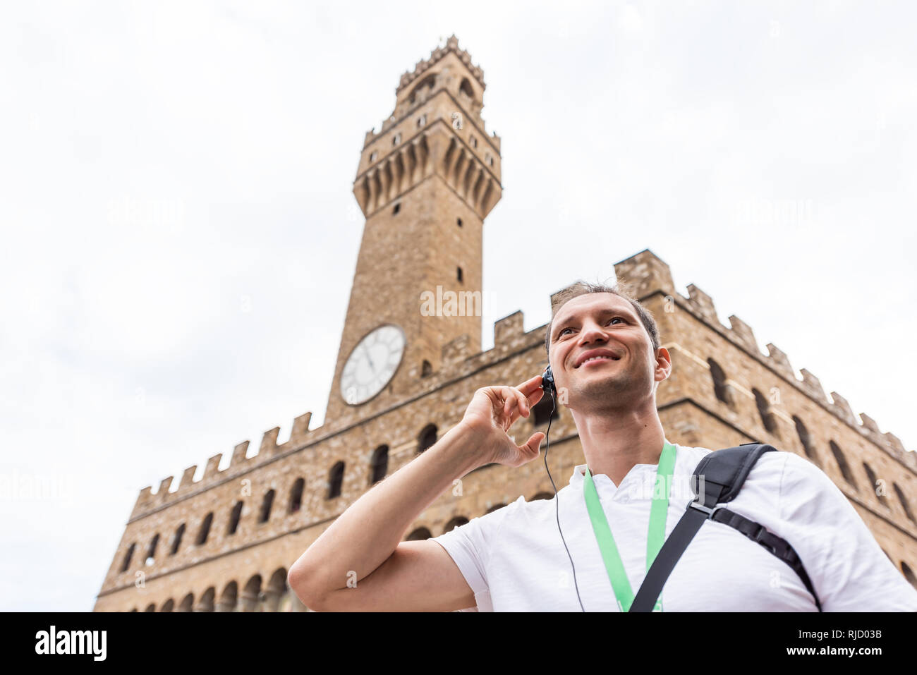 Firenze, Italy people person tourist listening to tour guide low angle view looking up by famous Florence old building Palazzo Vecchio - Stock Image