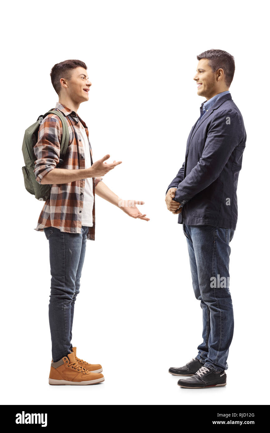Full length shot of a teenage male student talking to a young man isolated on white background - Stock Image