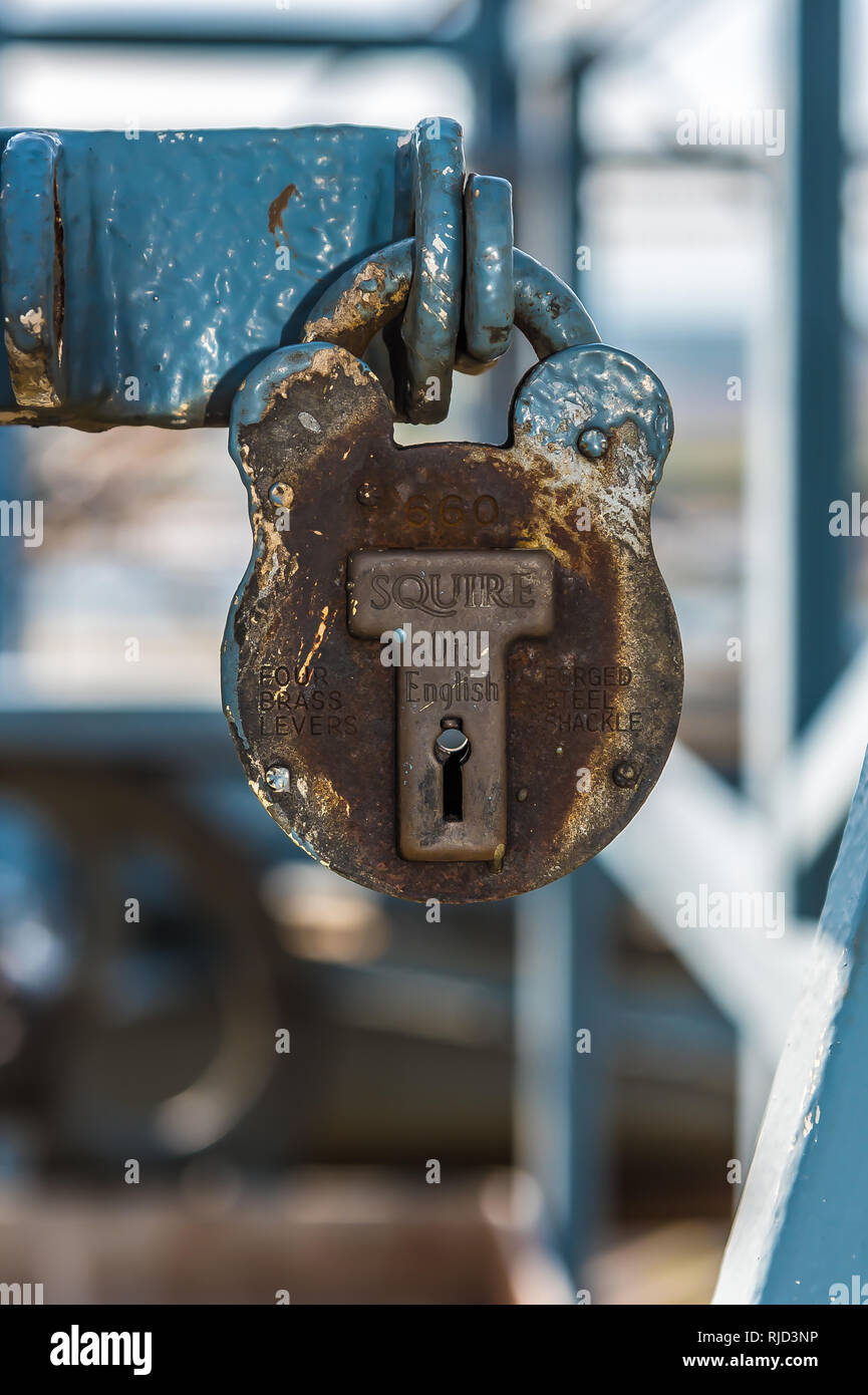 Old rusty padlock high on the Famous Transporter Bridge, Newport Wales UK  with peeling industrial blue paint daytime and close up shot. - Stock Image