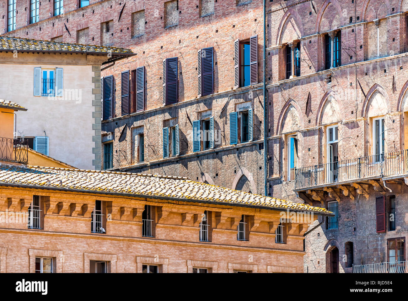 Siena, Italy Street in historic medieval old town village in Tuscany with facade exterior architecture on square during sunny summer day Stock Photo