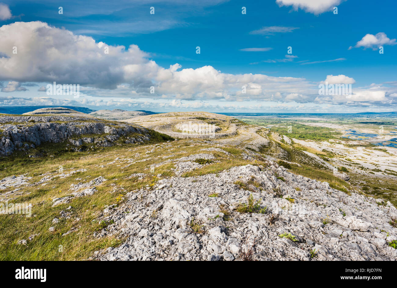 View from the top of Mullaghmore Mountain, The Burren, County Clare, Ireland, with Slieve Roe and the flat limestone pavement of the Gort Lowlands - Stock Image