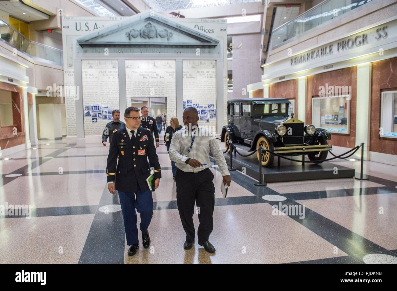 Maj. Harold Huff, training with industry USAA fellow (right) escorts Lt. Col. Chris Hyde through USAA's home campus corridors in San Antonio, Texas during a visit on January 18th. The goal of this fellowship was to allow a couple Soldiers to experience corporate America communication techniques and learn the relationship of their industry as it relates to the functions of Army Public Affairs. - Stock Image