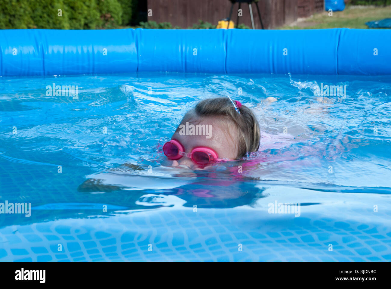 A young courageous swimmer dives in a garden pool. It's a hot summer afternoon. - Stock Image