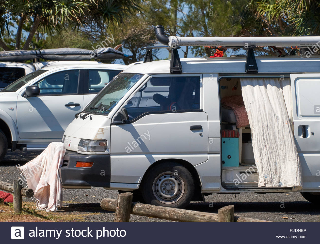 A small camper-van with it's side-door open, parked beside