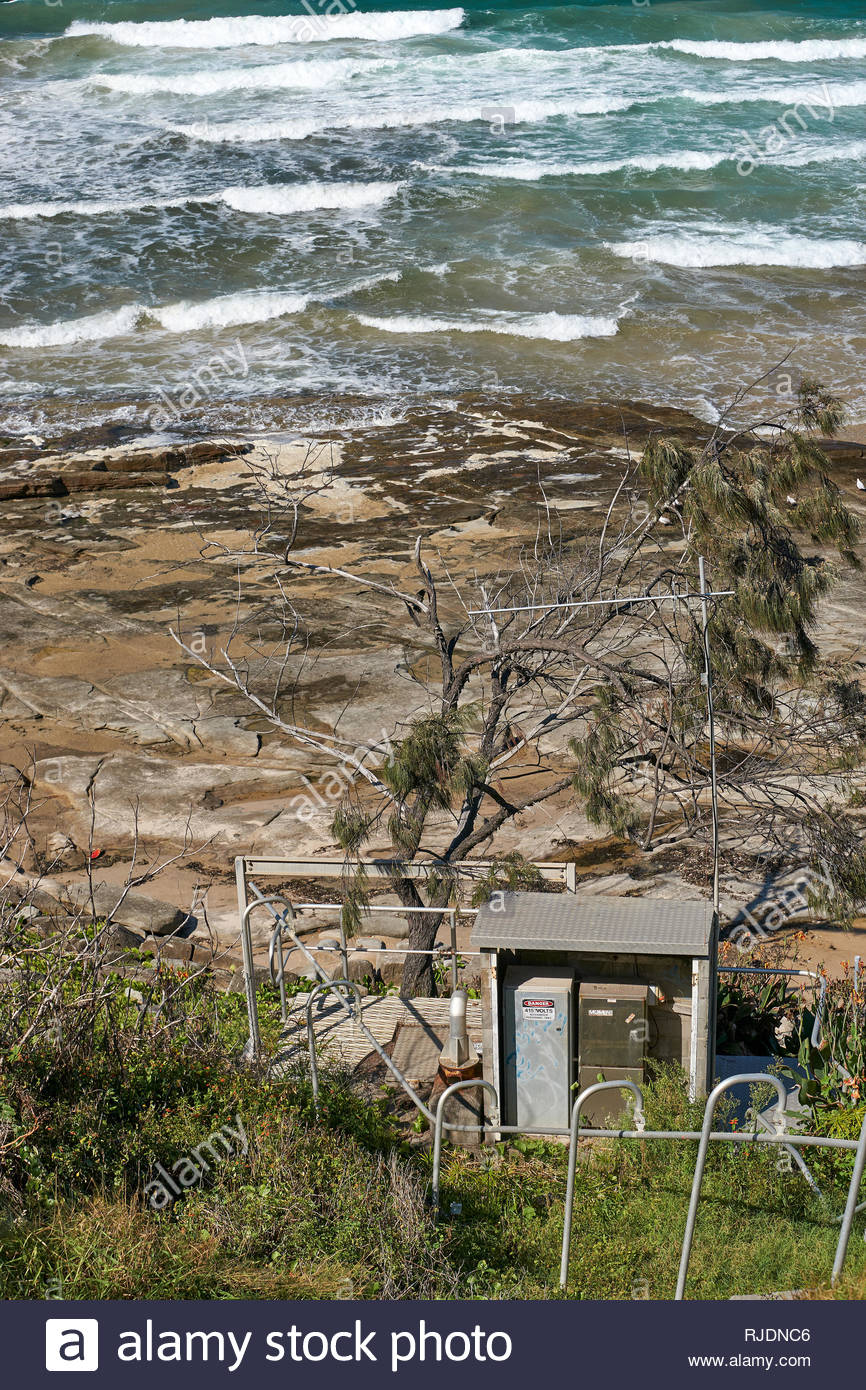 An electrical substation, located on the rocky foreshore of the Pacific Ocean; image taken during a hot summer's day in Yamba, NSW, Australia. - Stock Image