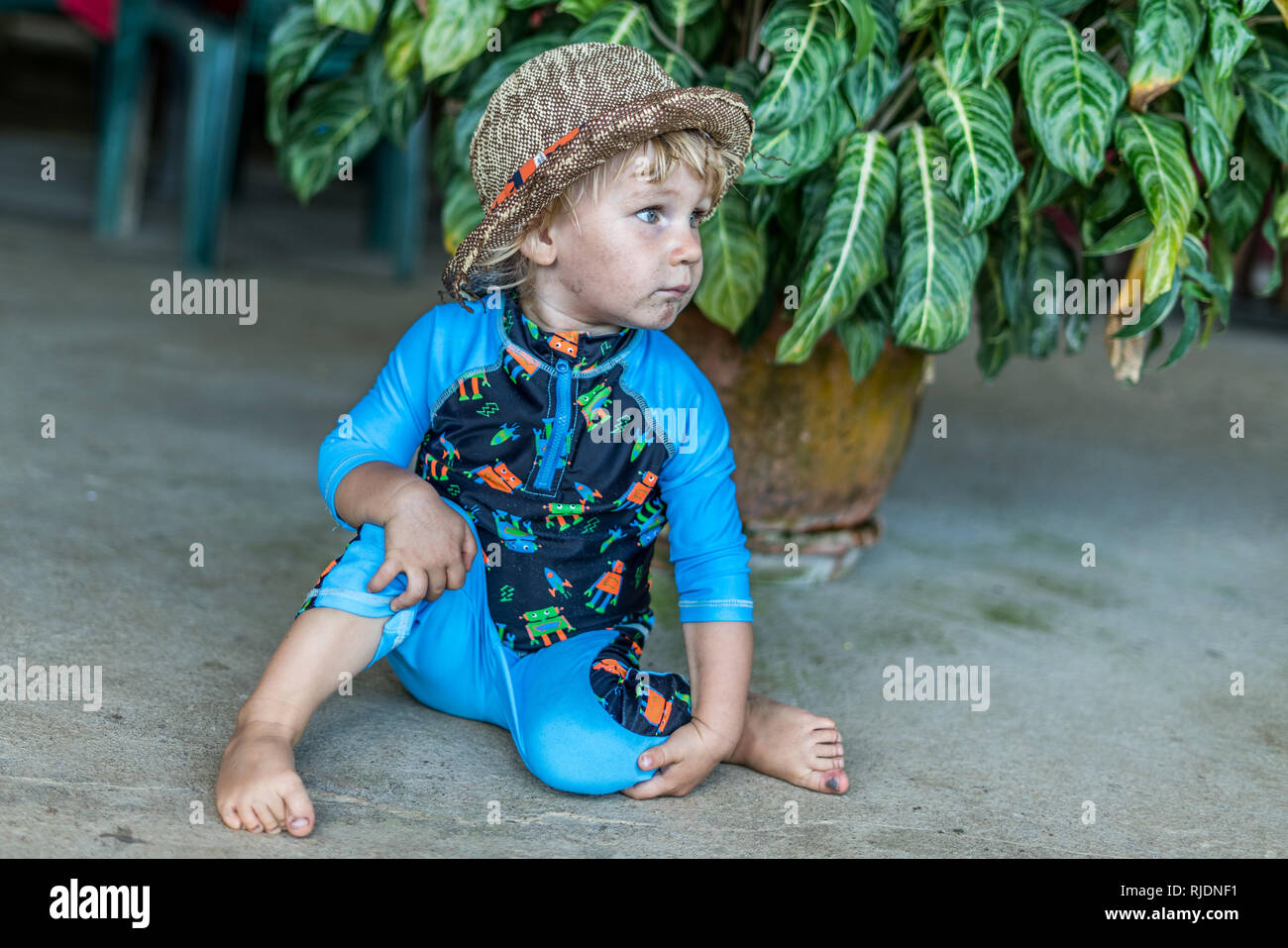 A nice portrait of a cute hat wearing baby boy posing in front of a beautiful tropical flower. The boy is wearing a UV protection suit. - Stock Image