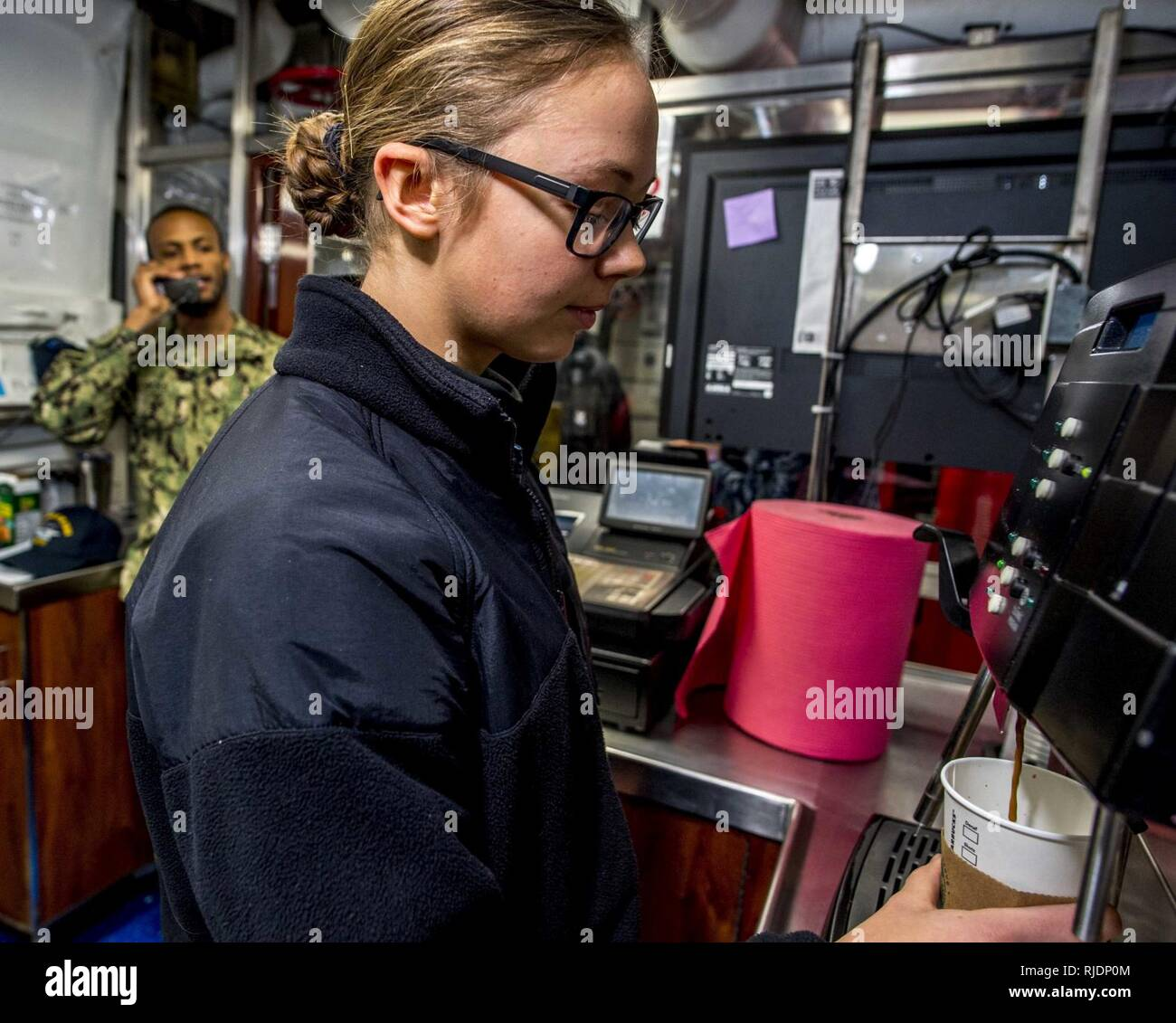 NORFOLK, Va (Jan. 22, 2018) Aviation Ordnanceman Airman Sarah Boone operates an espresso machine aboard the aircraft carrier USS George H.W. Bush (CVN 77). The ship is in port in Norfolk, Virginia, conducting routine maintenance in preparation for the Board of Inspection and Survey (INSURV). Stock Photo