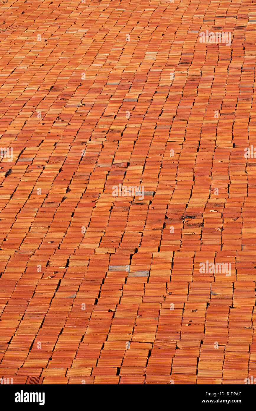 imperfect red bricks layed out in rows at an angle - Stock Image