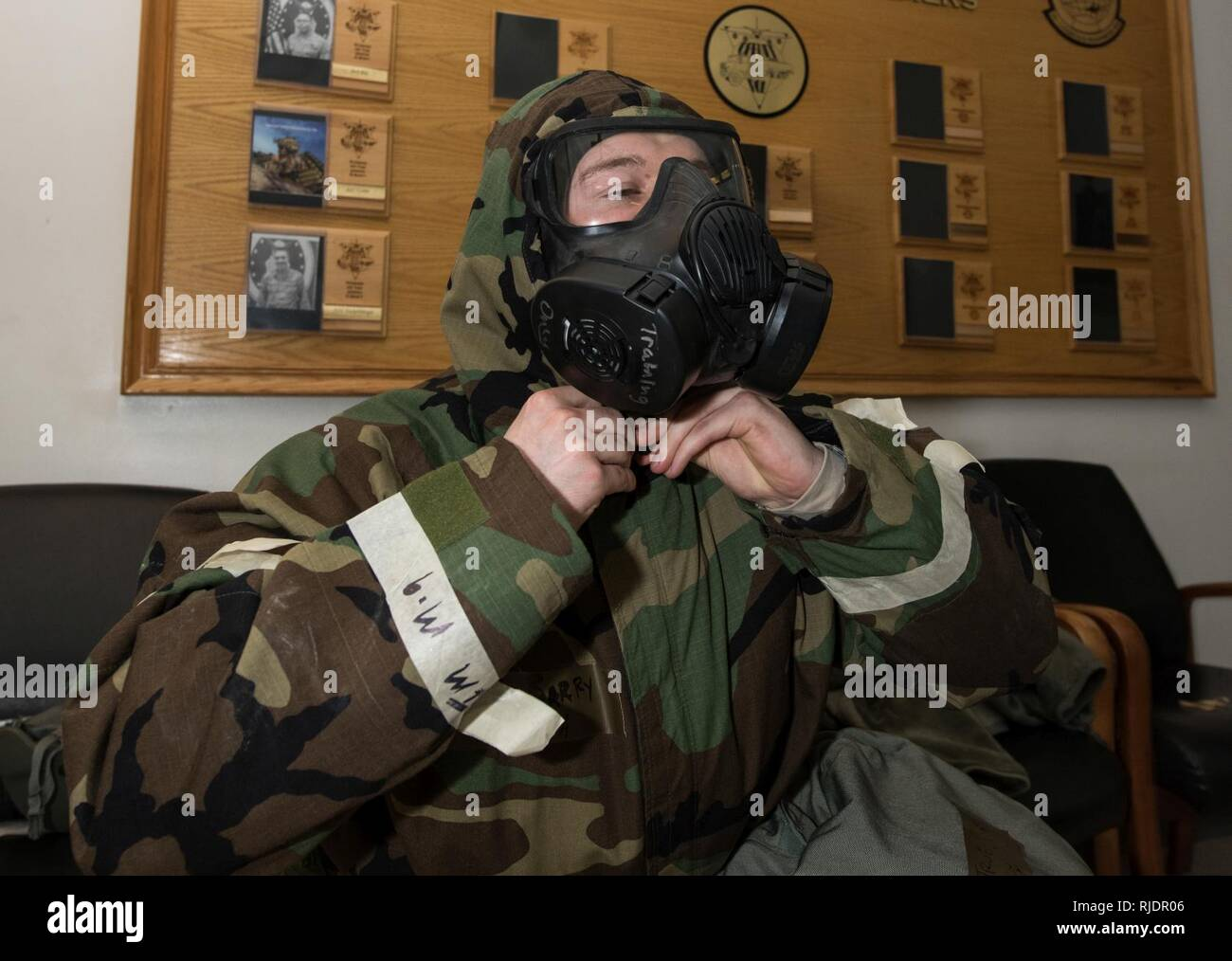 Senior Airman Barry Troe, 55th Logistics Readiness Squadron Fuels Management Flight distribution operator, dons his chemical protection overgarment (CPO) during an operational readiness exercise at Offutt Air Force Base, Nebraska, Jan. 23, 2018. The CPO is paired with an M50 Joint Service General Purpose mask and protective boots and gloves to protect against chemical, biological, radiological and nuclear hazards. - Stock Image