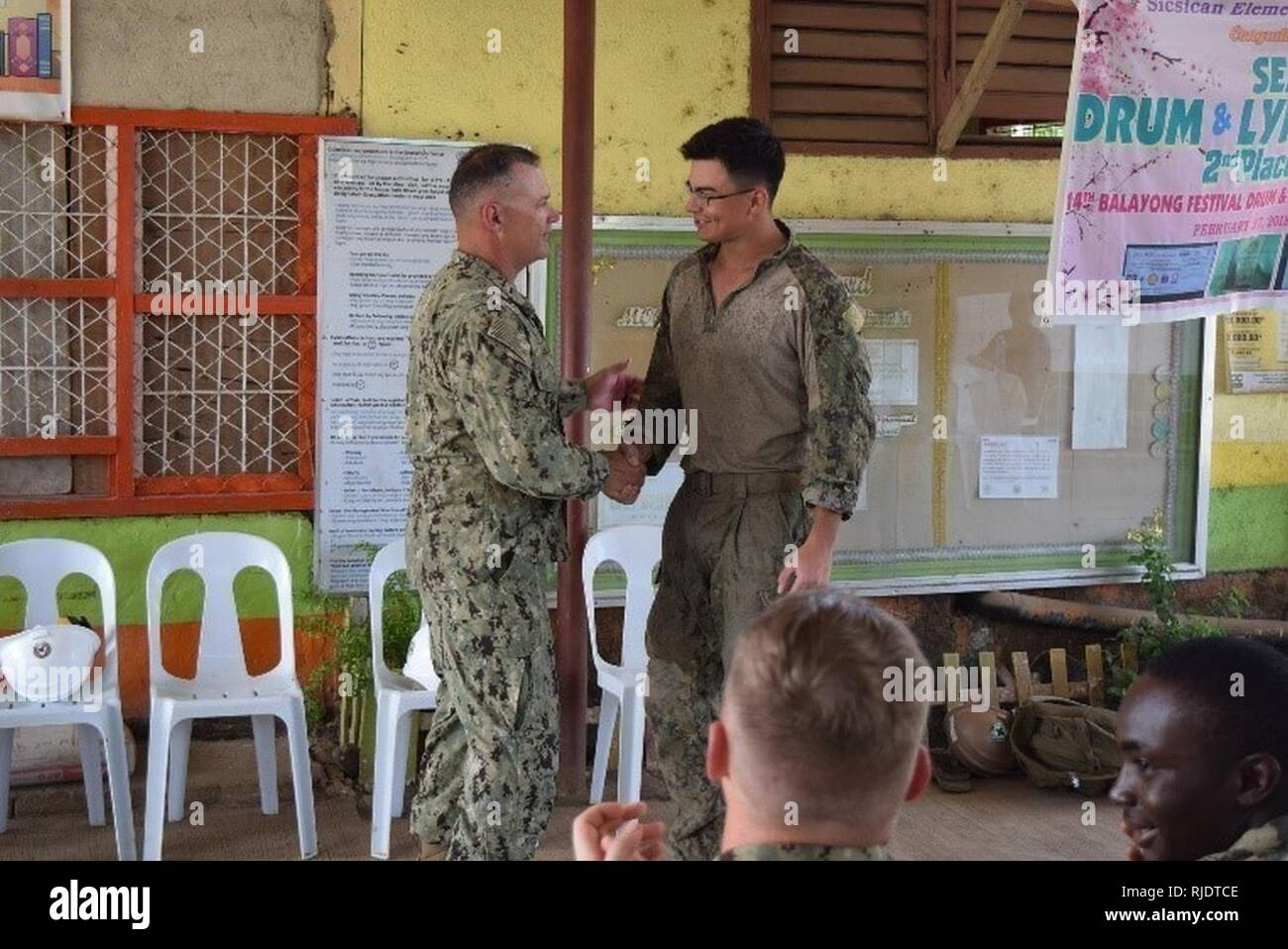 PALAWAN, Philippines (May 18, 2018) 30th Naval Construction Regiment Command Master Chief Joe Arnold presents Builder Constructionman Apprentice Chandler Cruz, assigned to Naval Mobile Construction Battalion (NMCB) 5, a coin in recognition of his efforts above and beyond expectations. NMCB 5 is forward deployed to execute construction, humanitarian and foreign assistance, and theater security cooperation support of United States Pacific Command. - Stock Image