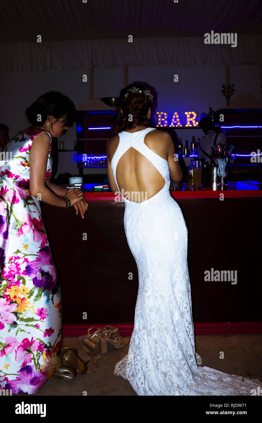 A bride on her wedding dress and a friend stand at the bar  at night. - Stock Image