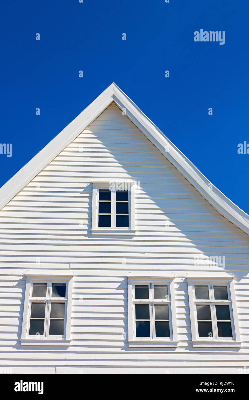 White wooden house gable against blue sky - Stock Image