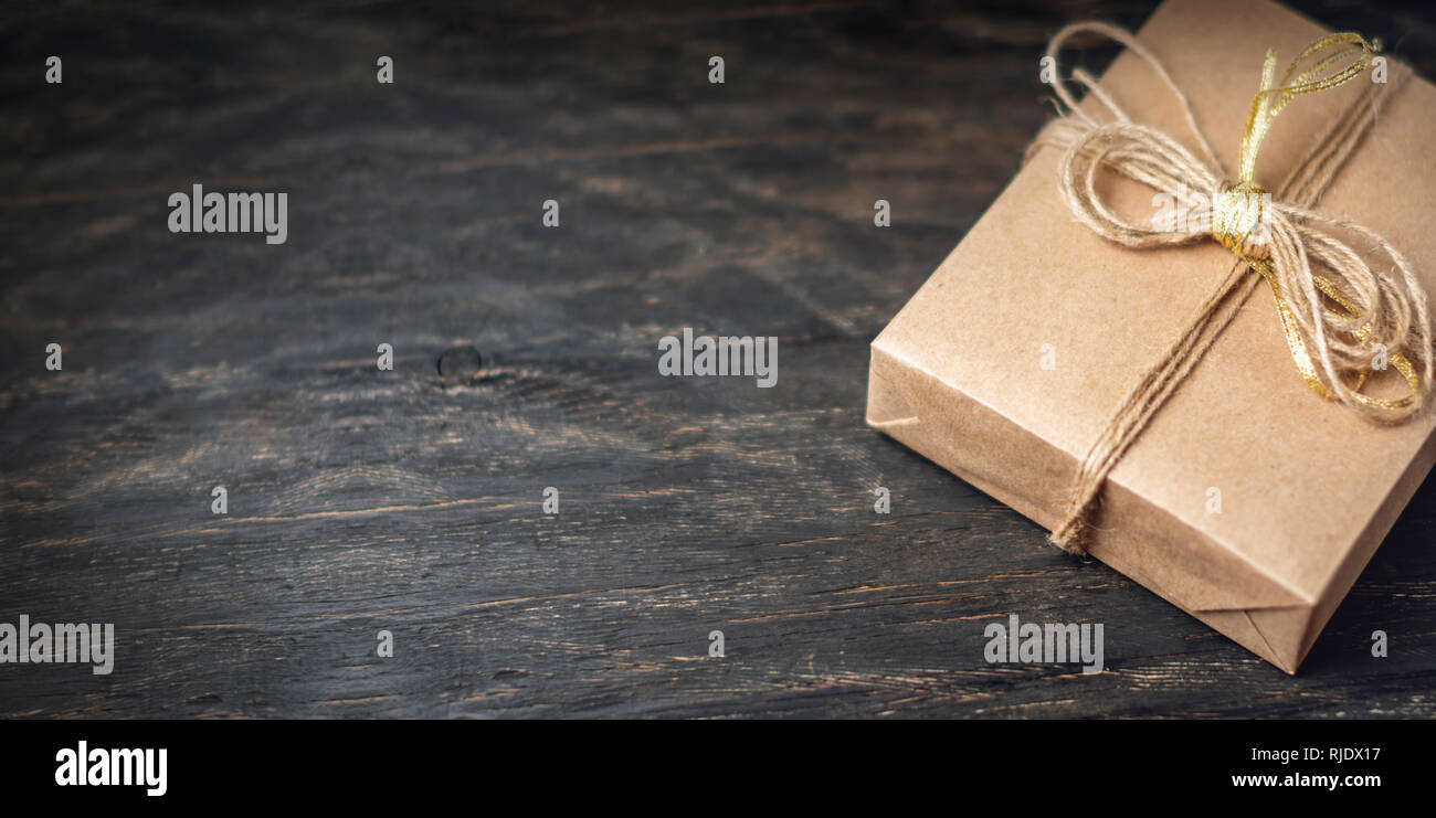 Holiday gift box Packed in crafting paper on dark wooden background. The concept of beautiful cards with gifts and place for text - Stock Image