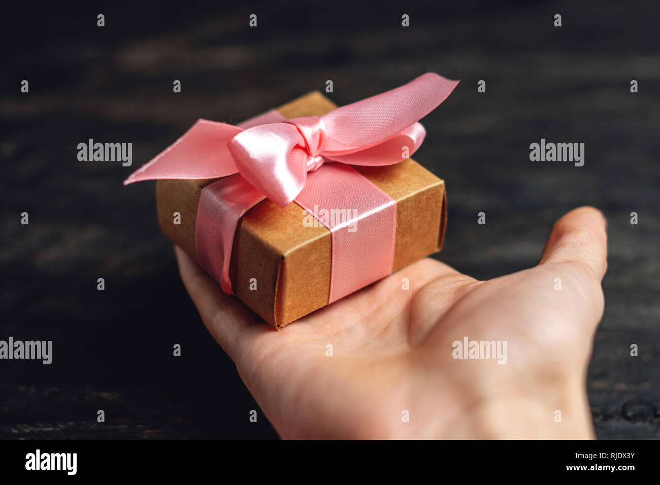 Hand holding Holiday gift box Packed in crafting paper with pink ribbon on dark wooden background. The concept of beautiful cards with gifts - Stock Image