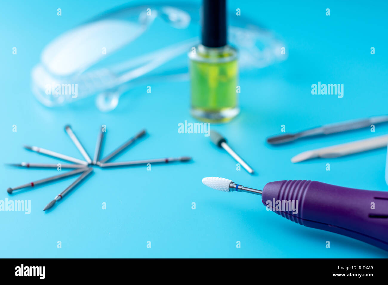 A set of cosmetic tools for professional hardware manicure on a blue background. Milling cutter, glasses, cuticle cleanser, top view - Stock Image