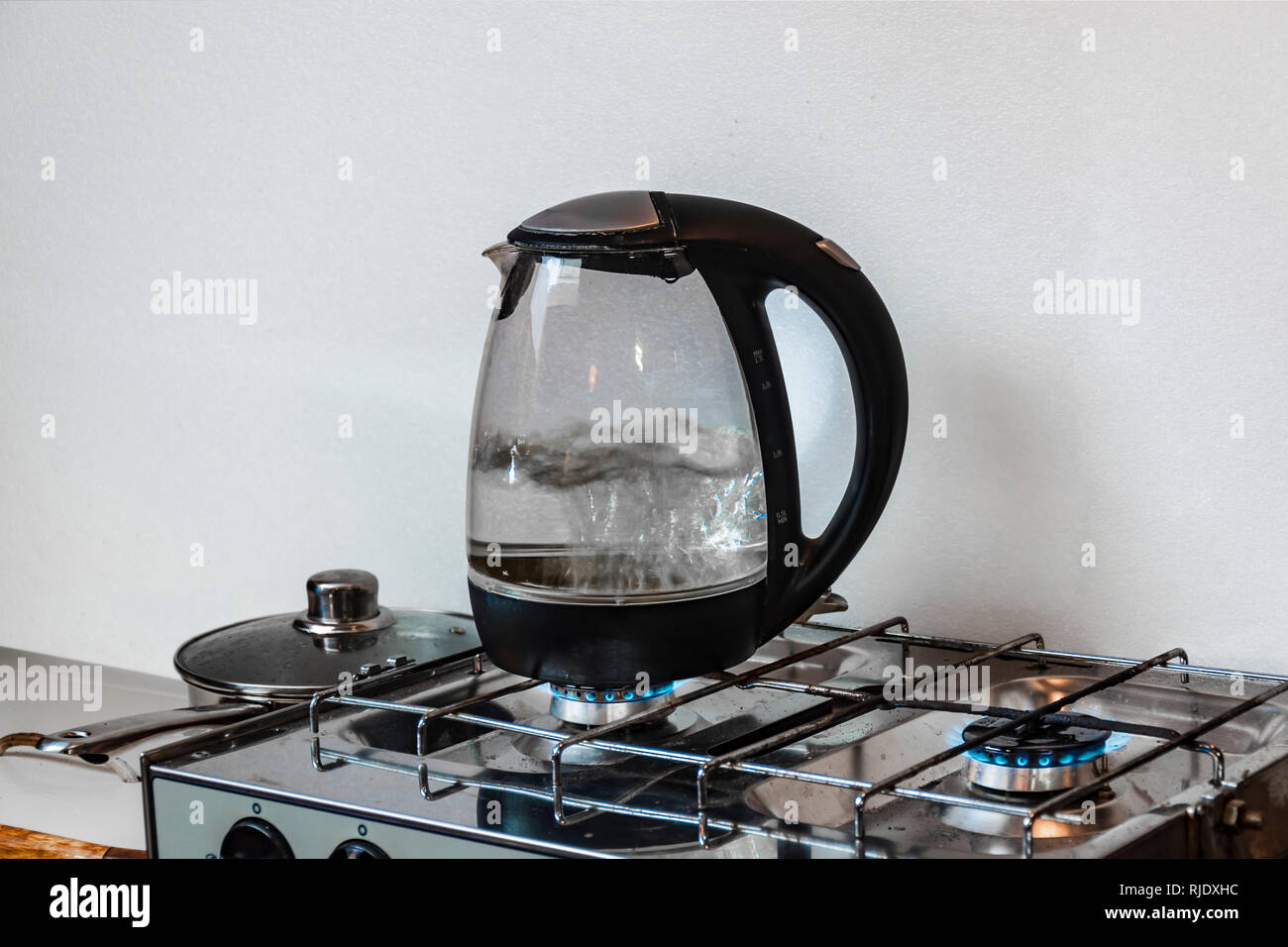 Rapid boiling. Modern electrical kettle boiling at gaz hob. - Stock Image