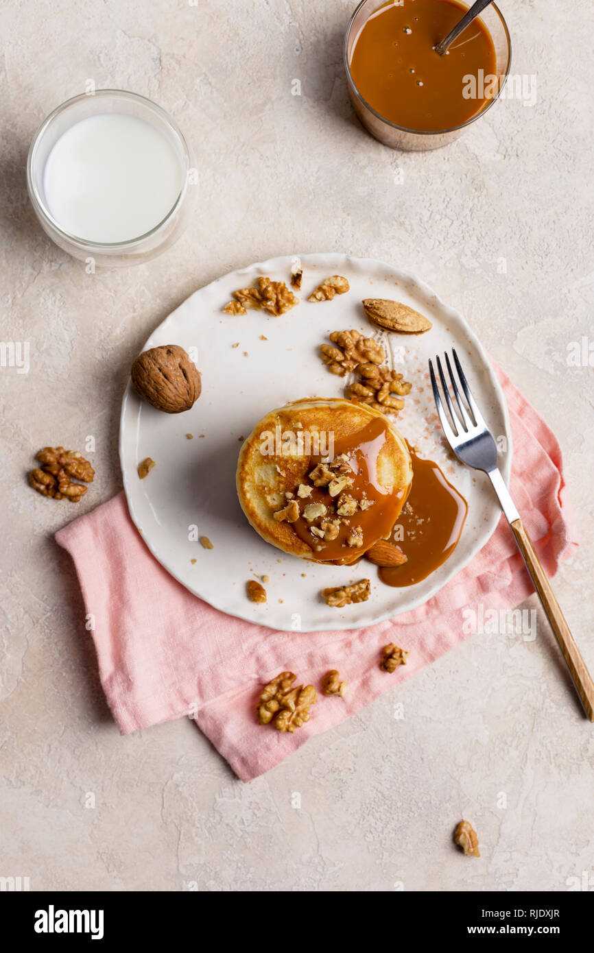 Healthy breakfast, stack of american pancakes with caramel souse and nuts at white plate with fork and pink napkin, top view - Stock Image