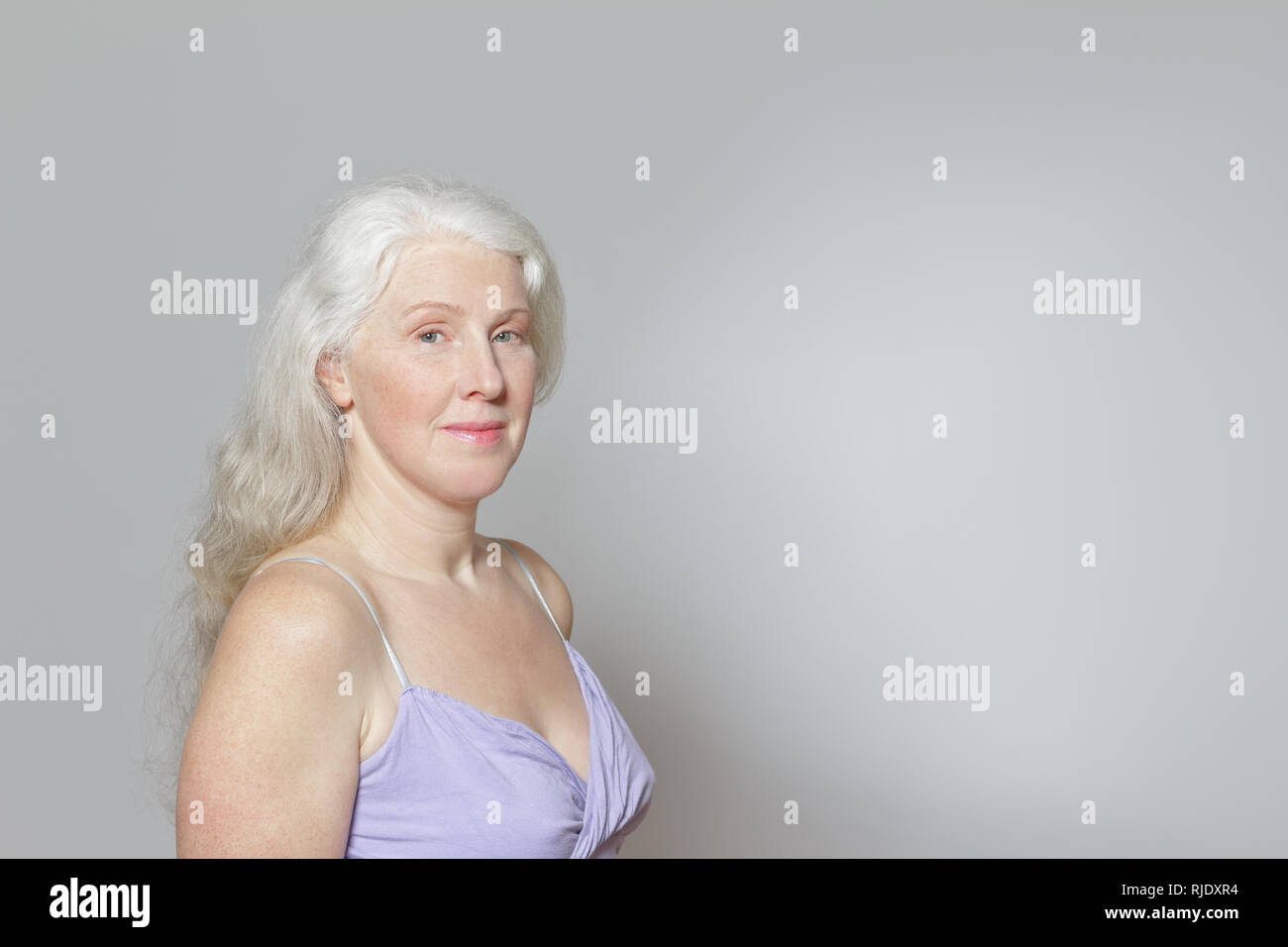 Headshot of a mature woman with freckles and shiny long gray hair in front of white background, copy space. Stock Photo