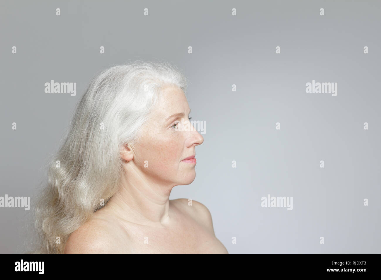 Side view of a mature woman with shiny long white hair, but without make-up, gray background, copy space. Stock Photo