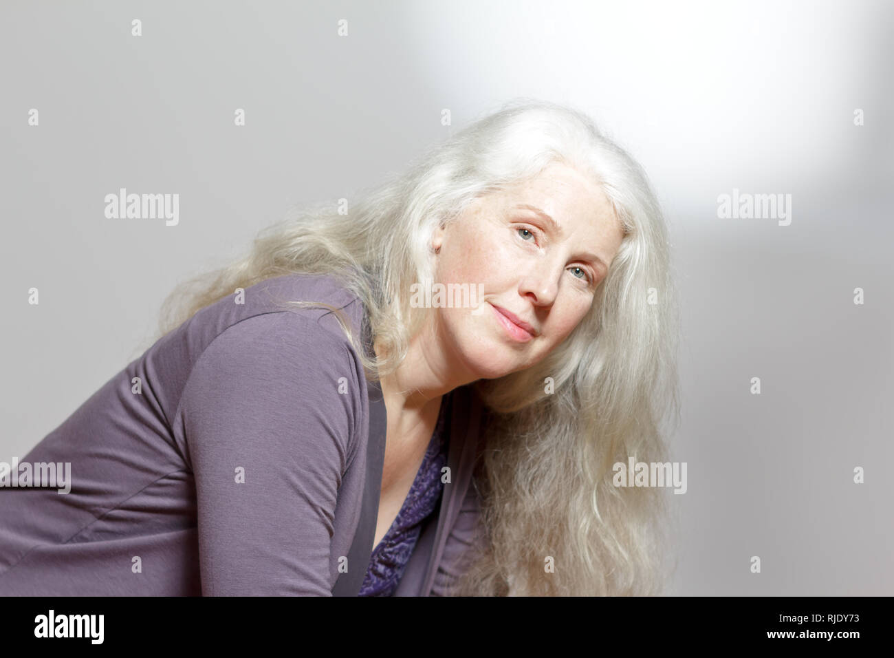 Headshot of an attractive mature woman with beautiful long gray hair in front of white background, copy space. Stock Photo
