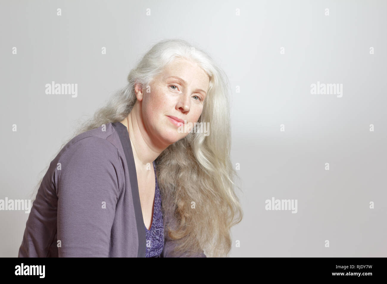 Portrait of an attractive mature woman with beautiful long gray hair in front of white background, copy space Stock Photo