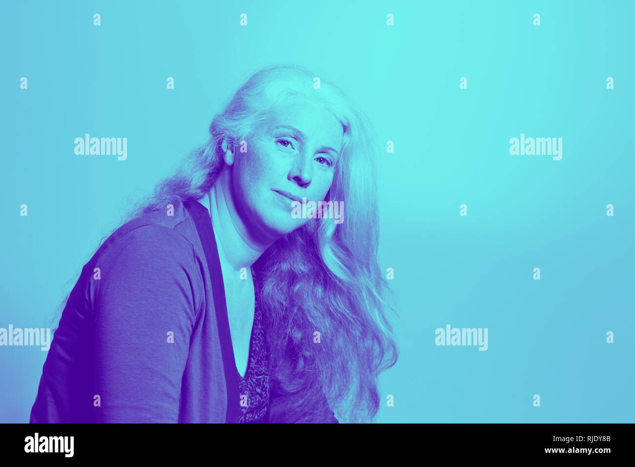 Portrait of a beautiful middle aged woman with long wavy hair in trendy duotone effect, copy space. Stock Photo