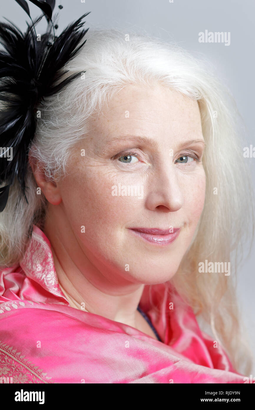 Glamour portrait of an attractive mature woman with gray hair wearing a pink scarf and a black feather fascinator. Stock Photo