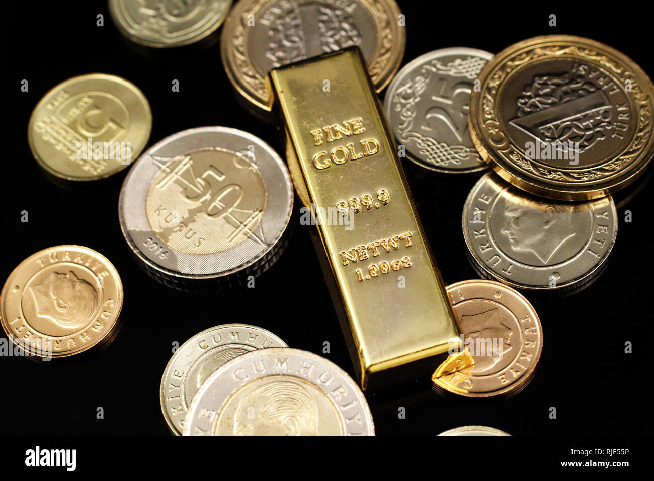 A macro image of an assortment of Turkish coins and a gold one ounce ingot on a reflective black background - Stock Image