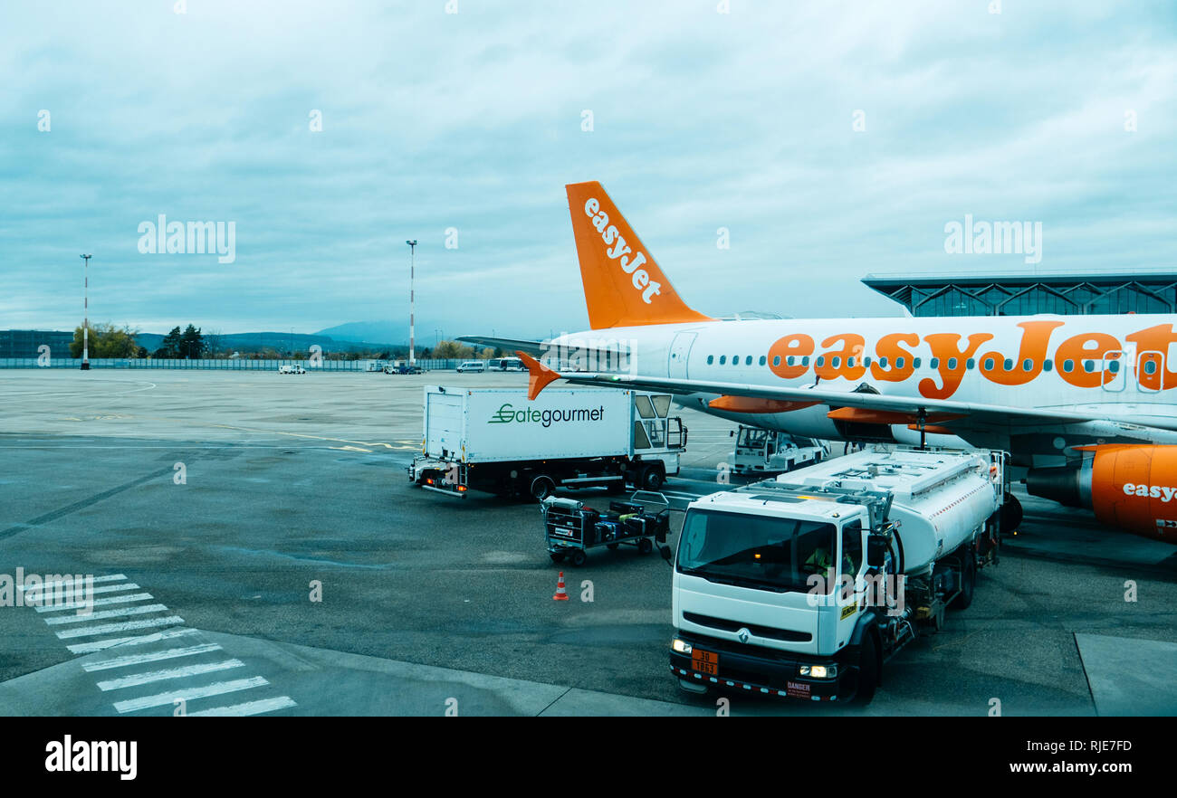 Basel, Switzerland - 11 Nov 2018: Aicraft operated by EasyJet airlines on tarmac of Basel Mulhouse International Airport being loaded with fuel and food - elevated view - Stock Image