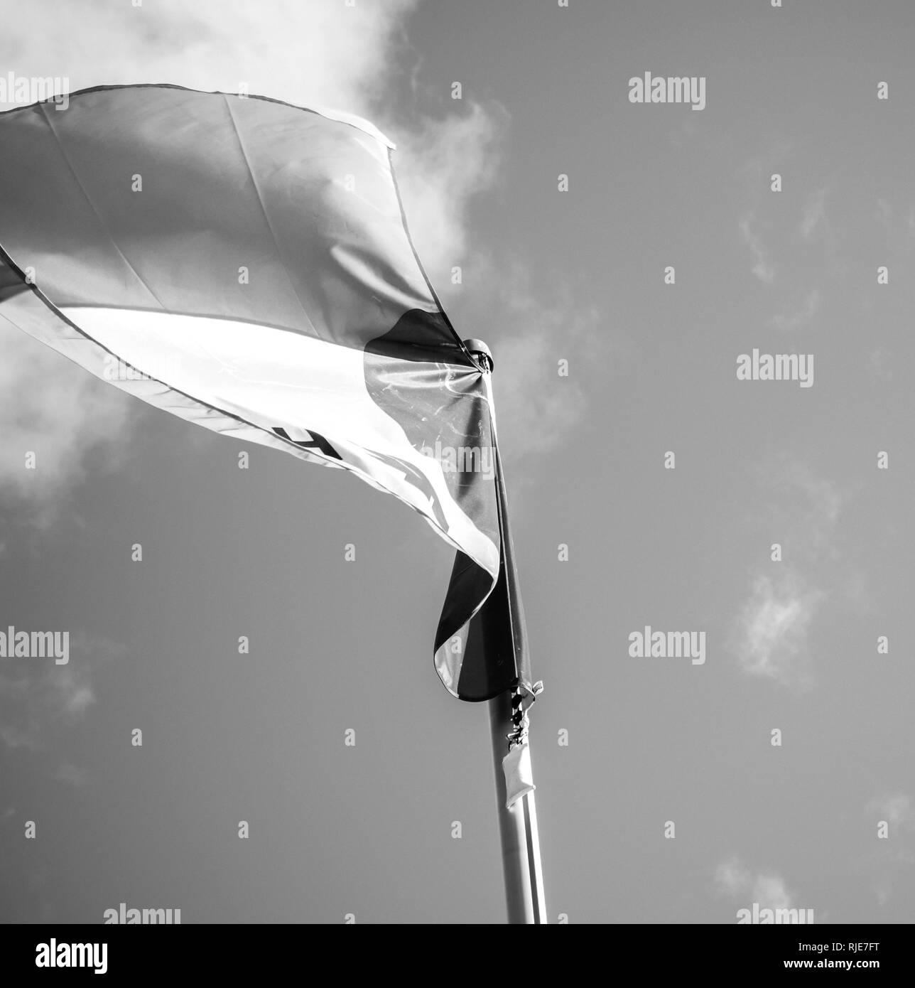 HAMBURG, GERMANY - MAR 20, 2018: Hapag-Lloyd transnational German-based transportation company flag waving against blue sky - black and white - Stock Image