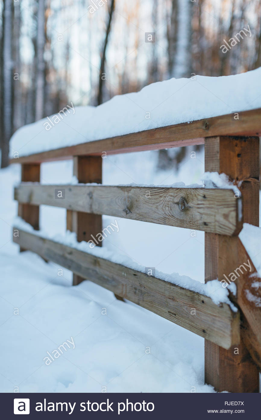 Photo of a wooden fence covered with snow, selective focus on the foreground, blurred background/ frosty winter day, cold snap, snowdrift. - Stock Image